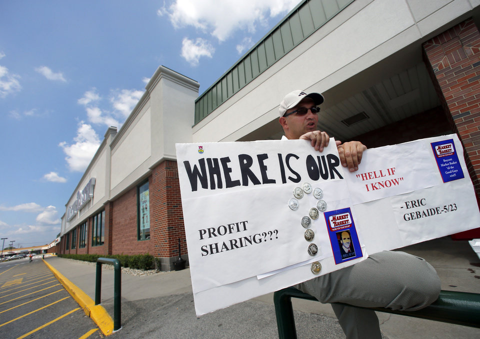 Photo - Carlton Pfeifer, an employee of Market Basket, holds a sign outside a supermarket in Danvers, Mass., Monday, Aug. 4, 2014. Executives at the troubled Market Basket supermarket chain in New England say they have heard from employees who are