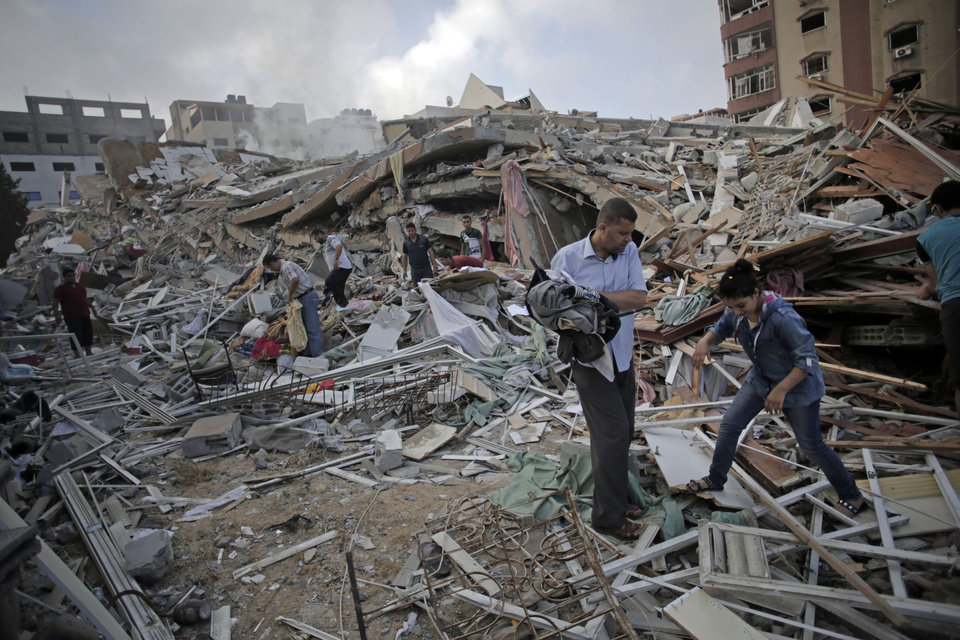 Photo - Palestinians inspect the rubble and salvage items from the Al-Zafer apartment tower following Israeli airstrikes Saturday that collapsed the 12-story building, in Gaza City, Sunday, Aug. 24, 2014. The army said the Gaza City apartment tower was targeted because a Hamas command center operated from there. The weekend strikes by Israel marked the first time large buildings were toppled signaling a new escalation in seven weeks of fighting with Hamas. (AP Photo/Khalil Hamra))