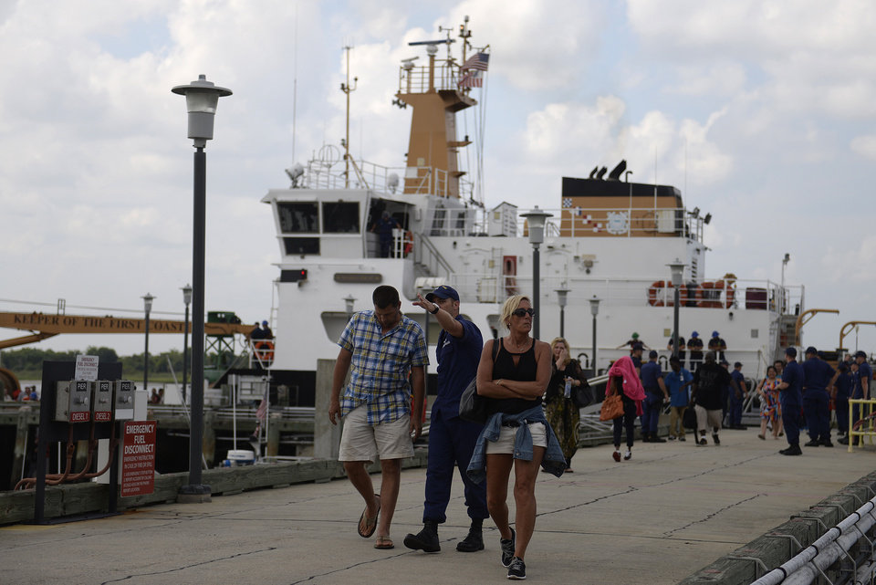Photo - Passengers from the Escapade casino boat disembark from the Maria Bray at the U.S. Coast Guard station at Tybee Island, Ga. on Wednesday, July 16, 2014. The boat became grounded on a sandbar between Tybee Island and Hilton Head Island Tuesday evening. Passengers and crew remained on the boat for 16 hours before the U.S. Coast Guard evacuated them. (AP Photo/The Morning News, Brittney Lohmiller)