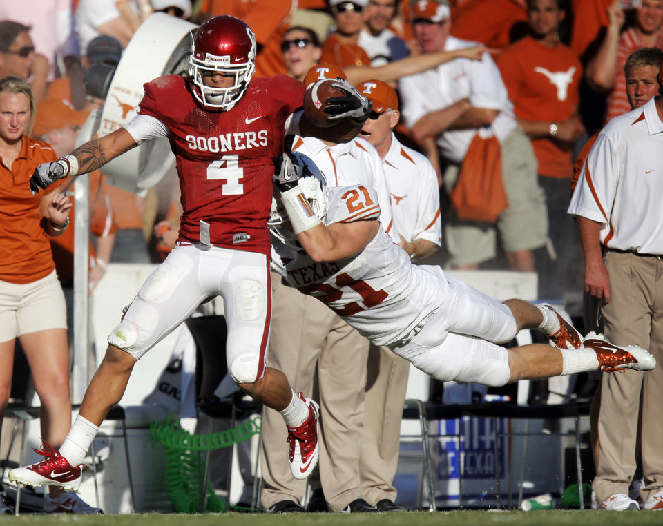 OU's Kenny Stills (4) is brought down by Blake Gideon (21) of Texas after a reception in the fourth quarter during the Red River Rivalry college football game between the University of Oklahoma Sooners (OU) and the University of Texas Longhorns (UT) at the Cotton Bowl on Saturday, Oct. 2, 2010, in Dallas, Texas. OU won, 28-20. Photo by Nate Billings, The Oklahoman