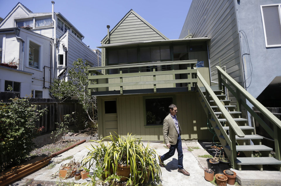 Photo - George Limperis, a realtor with Paragon Real Estate Group, walks in the backyard of a property in the Noe Valley neighborhood in San Francisco, Wednesday, July 30, 2014. In the souped-up world of San Francisco real estate a $1 million will barely cover the cost of an 800-square-foot starter home that needs work and may or may not include private parking. (AP Photo/Jeff Chiu)