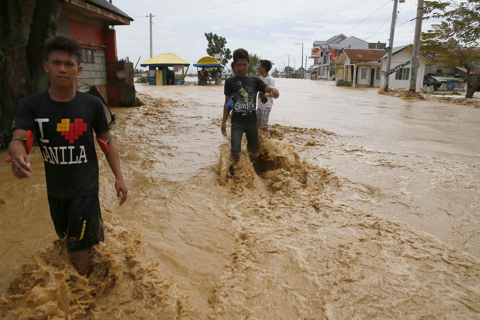 Photo - Residents wade through floodwaters brought about by Typhoon Koppu at Zaragosa township, Nueva Ecija province, north of Manila, Philippines Monday, Oct. 19, 2015. Slow-moving Typhoon Koppu blew ashore with fierce wind in the northeastern Philippines early Sunday, toppling trees and knocking out power and communications and forcing the evacuation of thousands of villagers.(AP Photo/Bullit Marquez)