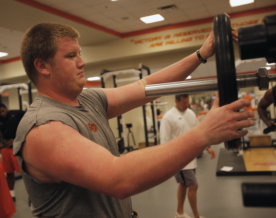 Photo - OKLAHOMA STATE UNIVERSITY / COLLEGE FOOTBALL: Jake Jenkins, sophomore, puts weights on a bar during the OSU football team's strength and conditioning training at Boone Pickens  Stadium in Stillwater, Okla., Tuesday, July 17, 2012.  Photo by Garett Fisbeck, The Oklahoman