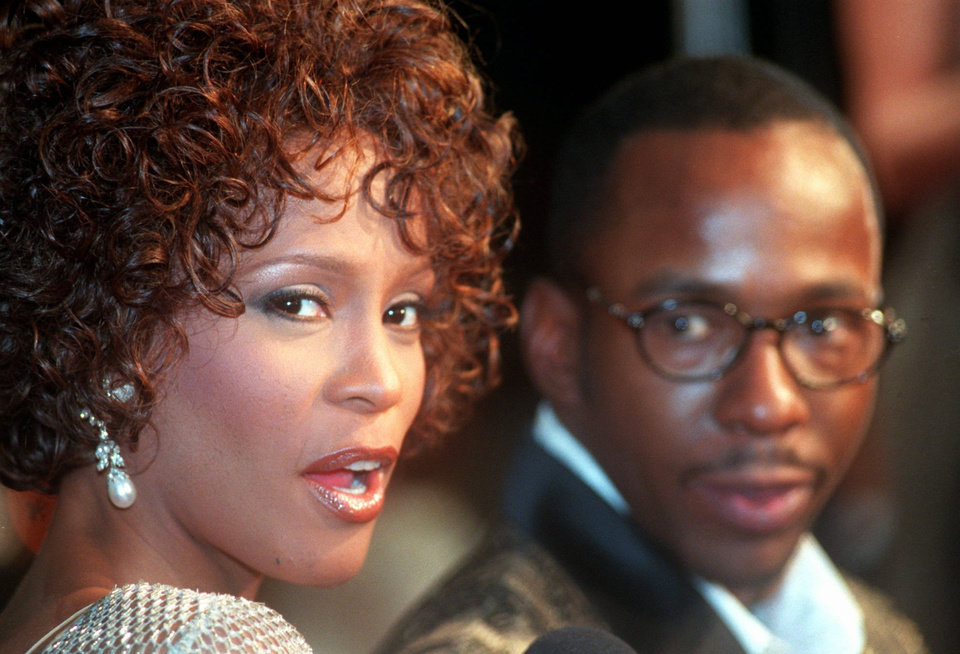 "FILE - In this Oct. 13, 1997 file photo, Whitney Houston looks over her shoulder as her husband Bobby Brown looks to her at the premiere of ""The Wonderful World of Disney"" movie ""Cinderella,"" at Mann's Chinese Theater in the Hollywood section of Los Angeles, Whitney Houston, who reigned as pop music's queen until her majestic voice and regal image were ravaged by drug use, has died, Saturday, Feb. 11, 2012. She was 48. (AP Photo/Rene Macura, File) ORG XMIT: NY135"