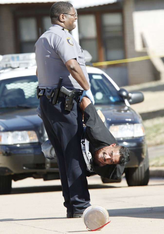 An Oklahoma City Police Officer carries a handcuffed George Rodriguez to a police car near 2200 SE 47th after being arrested in Oklahoma City, March 09, 2010. Rodriguez was arrested at the scene after a woman was set ablaze. Photo by Steve Gooch, The Oklahoman
