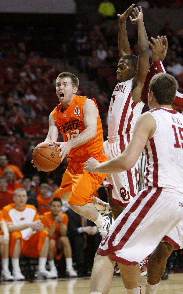 Oklahoma State's Keiton Page (12) goes past Oklahoma's Sam Grooms (1) during the Bedlam men's college basketball game between the University of Oklahoma Sooners and the Oklahoma State Cowboys in Norman, Okla., Wednesday, Feb. 22, 2012. Oklahoma won 77-64.  Photo by Bryan Terry, The Oklahoman