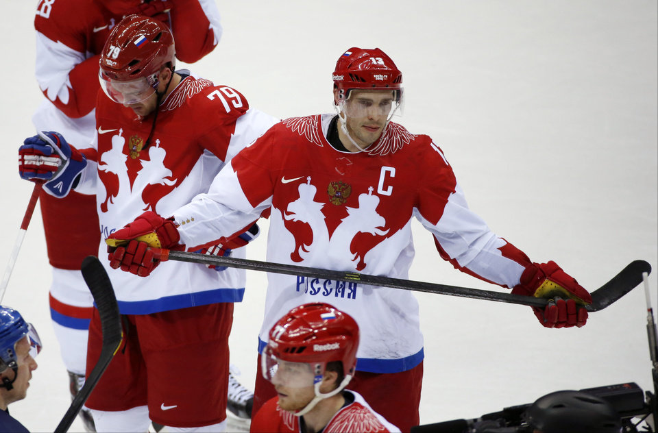 Photo - Russia defenseman Andrei Markov, left, and forward Pavel Datsyuk react after Russia lost 3-1 to Finland in a men's quarterfinal ice hockey game at the 2014 Winter Olympics, Wednesday, Feb. 19, 2014, in Sochi, Russia. (AP Photo/Mark Humphrey)