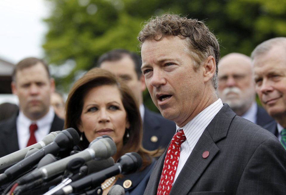 Photo - Rep. Michele Bachmann, R-Minn., chairwoman of the Tea Party Caucus, listens at left as while Sen. Rand Paul, R-Ky., speaks during a news conference with Tea Party leaders about the IRS targeting Tea Party groups, Thursday, May 16, 2013, on Capitol Hill in Washington. (AP Photo/Molly Riley)