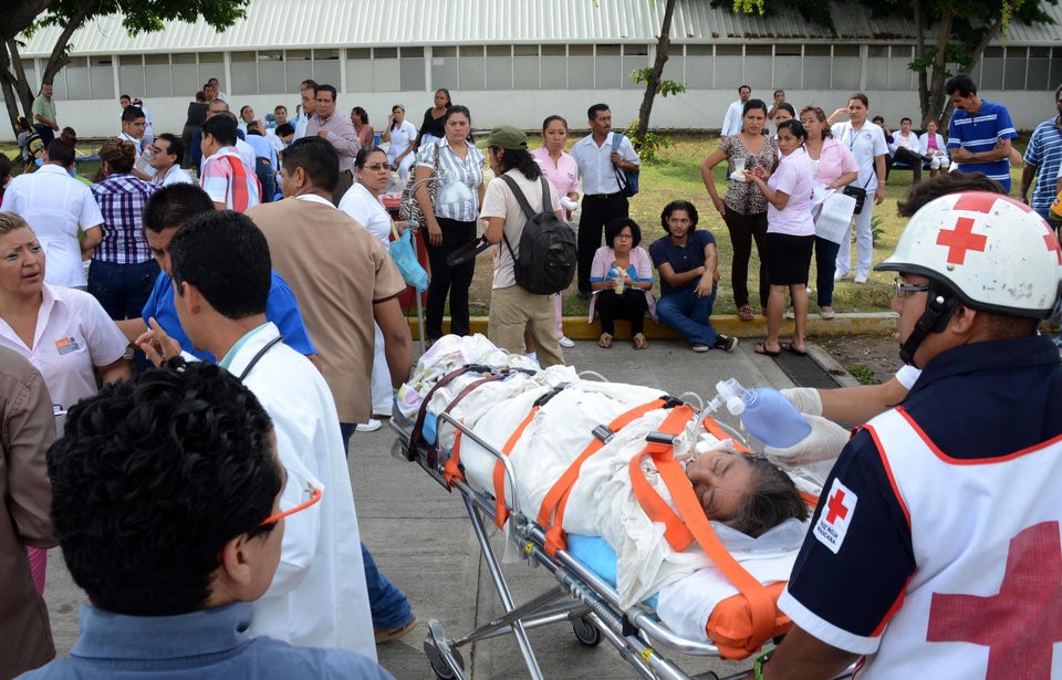 Photo - A patient is evacuated from a hospital after an earthquake in Acapulco, Mexico, Wednesday, Aug. 21, 2013. The U.S. Geological Survey said the quake had a magnitude of 6.2 and was centered on the Pacific coast. (AP Photo/Bernardino Hernandez)