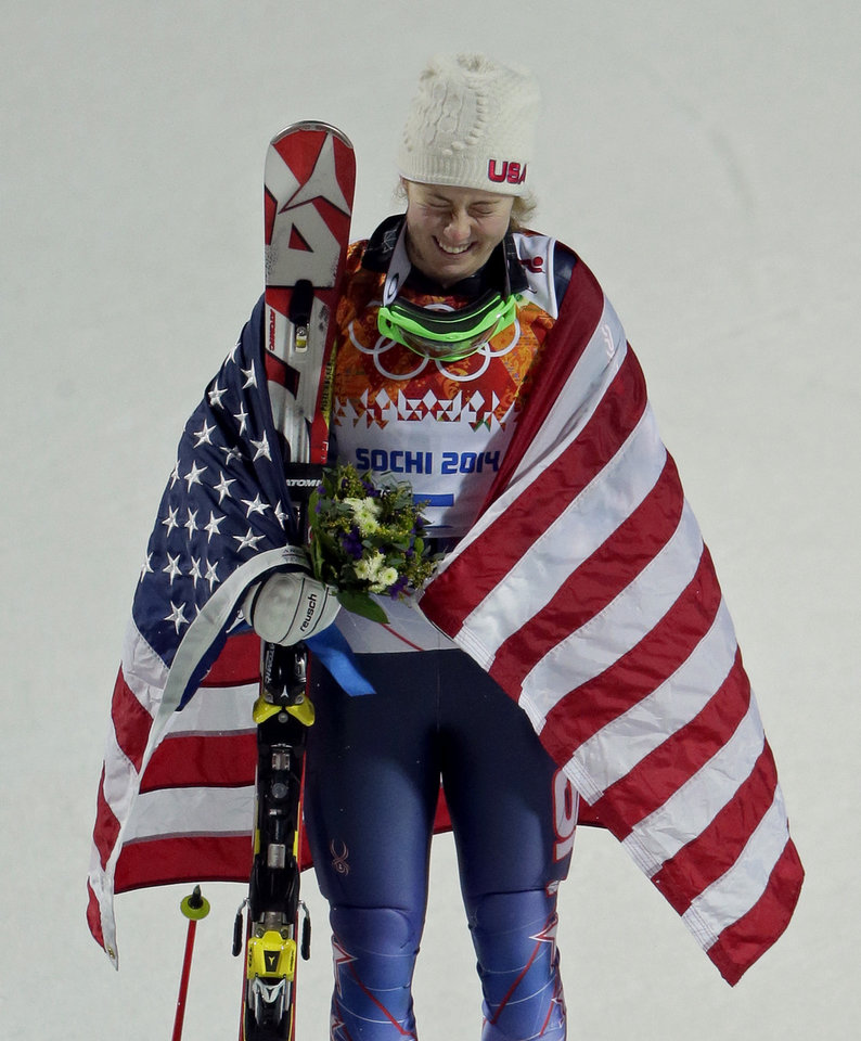 Photo - Women's gold medalist, United States' Mikaela Shiffrin, reacts after dropping her ski pole during the flower ceremony for the women's slalom at the Sochi 2014 Winter Olympics, Friday, Feb. 21, 2014, in Krasnaya Polyana, Russia. (AP Photo/Charlie Riedel)