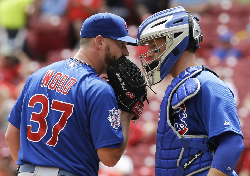 Photo - Chicago Cubs starting pitcher Travis Wood (37) talks with catcher John Baker in the fifth inning of a baseball game against the Cincinnati Reds, Tuesday, July 8, 2014, in Cincinnati. (AP Photo/Al Behrman)
