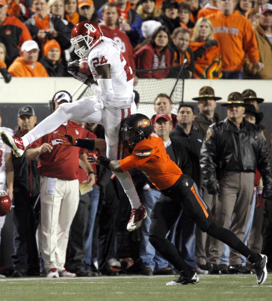 Oklahoma's Dejuan Miller (24) catches the ball as Oklahoma State's Justin Gilbert (4) tackles him during the Bedlam college football game between the Oklahoma State University Cowboys (OSU) and the University of Oklahoma Sooners (OU) at Boone Pickens Stadium in Stillwater, Okla., Saturday, Dec. 3, 2011. Photo by Sarah Phipps, The Oklahoman