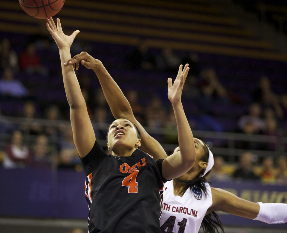 Photo - Oregon State's Breanna Brown (4) is fouled by South Carolina's Alaina Coates (41 during the first half of a second-round game of the NCAA women's college basketball tournament, Tuesday, March 25, 2014, in Seattle. (AP Photo/The Oregonian, Randy L Rasmussen) MAGS OUT, TV OUT, LOCAL TV AND INTERNET OUT, (THE MERCURY, WILLAMETTE WEEK, PAMPLIN MEDIA GROUP OUT)