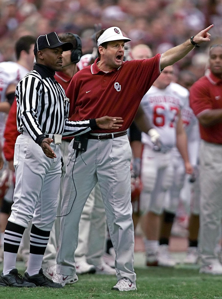 Photo - OU VS TEXAS A&M FOOTBALL:   Coach Bob Stoops is restrained from running on the field in the fourth quarter.  Staff photo by Steve Sisney