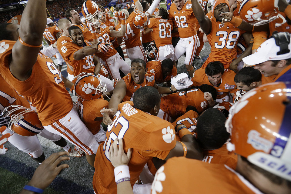 Photo - Clemson players pile up in the middle of the field after the Chick-fil-A Bowl NCAA college football game against LSU, Monday, Dec. 31, 2012, in Atlanta. Clemson won 25-24 on a field goal as time expired. (AP Photo/David Goldman)