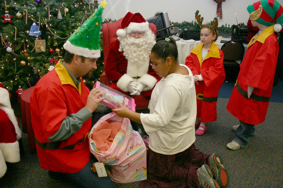 Santa Claus and his little helpers watch as Oklahoma Municipal Contractors Association (OMCA) elf, Shawn Freeman, helps J. D. McCarty Center patient Portia Thomas with her bag of gifts from Santa. Santa and his elves made an early stop in Norman for the OMCA annual Christmas party for the inpatients of the McCarty Center. The OMCA has been hosting this party for the McCarty Center for about 40 years. Community Photo By: Greg Gaston Submitted By: Greg,