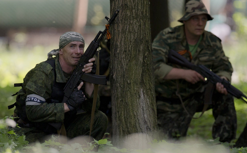 Photo - A pro-Russian gunman takes cover behind a tree during shooting near the airport, outside Donetsk, Ukraine, on Monday, May 26, 2014. Ukraine's military launched air strikes Monday against separatists who had taken over the airport in the eastern capital of Donetsk in what appeared to be the most visible operation of the Ukrainian troops since they started a crackdown on insurgents last month. (AP Photo/Vadim Ghirda)