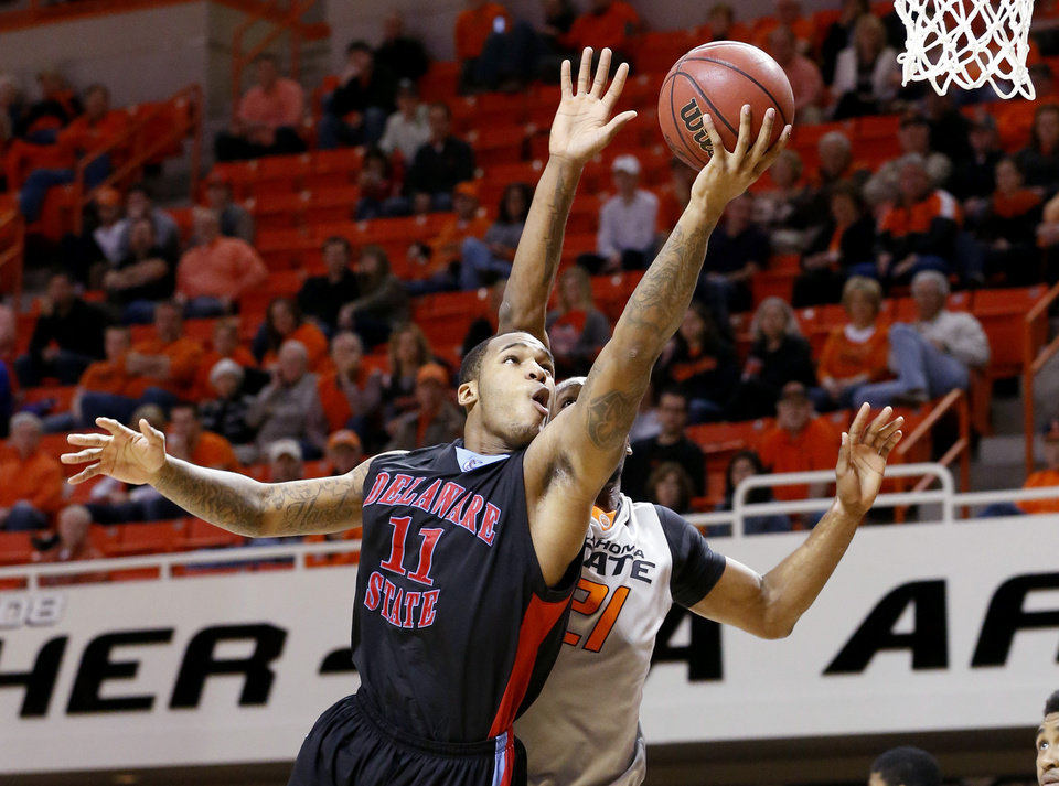 Photo - Delaware State guard DeAndre Haywood (11) shoots in front of Oklahoma State post Kamari Murphy (21) in the first half of an NCAA college basketball game in Stillwater, Okla., Tuesday, Dec. 17, 2013. Oklahoma State won 75-43. (AP Photo/Sue Ogrocki)