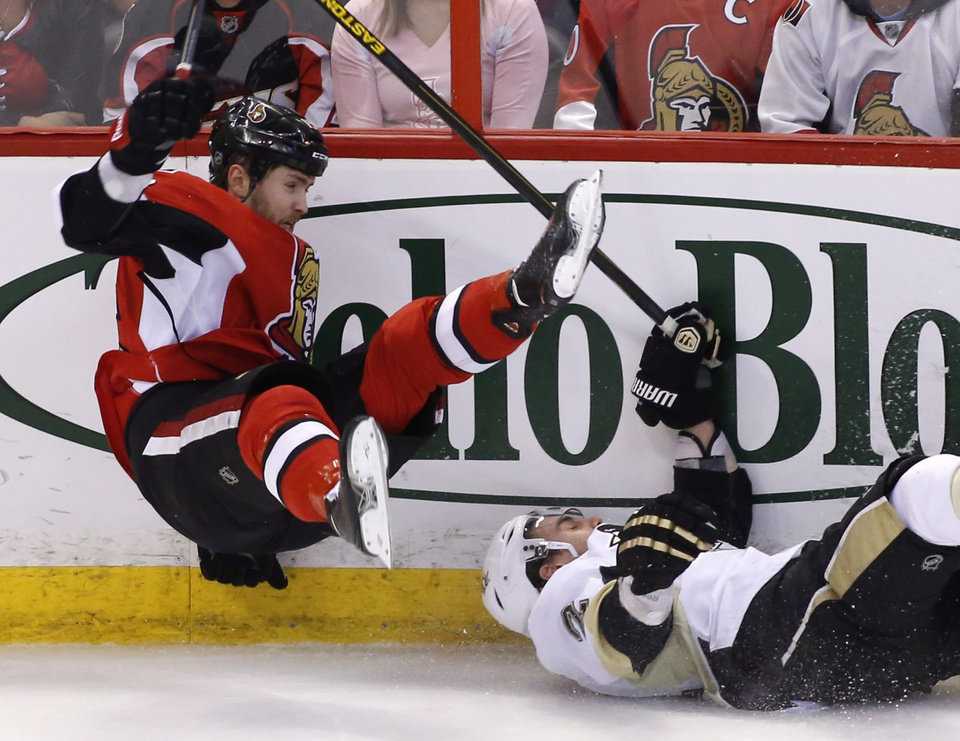 Photo - Ottawa Senators' Zack Smith, left, trips over Pittsburgh Penguins' Matt Niskanen during the first period of Game 4 of their NHL Stanley Cup Eastern Conference semifinal NHL hockey series in Ottawa on Sunday, May 19, 2013. (AP Photo/The Canadian Press, Patrick Doyle)