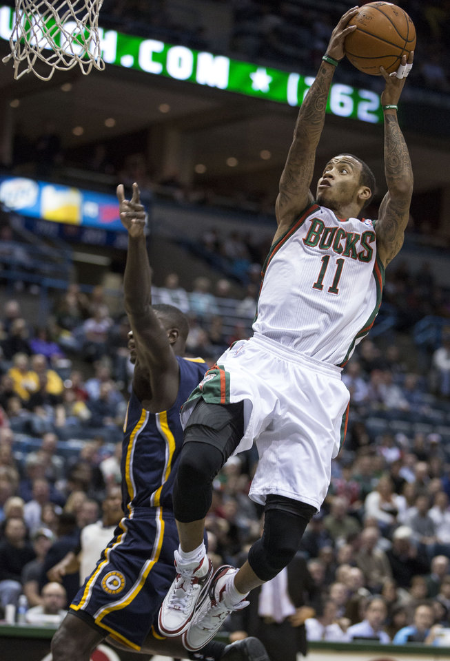 Milwaukee Bucks\' Monta Ellis, right, leaps through the lane for a layup against the Indiana Pacers defense during the first half of an NBA basketball game on Wednesday, Nov. 14, 2012, in Milwaukee. (AP Photo/Tom Lynn)