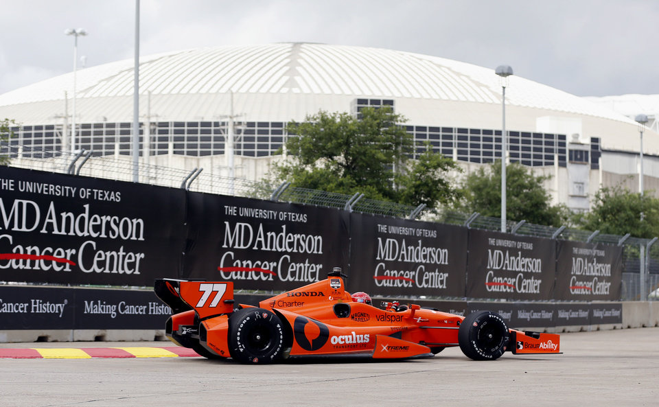 Photo - Simon Pagenaud, of France, drives near the Astrodome during a practice session for the IndyCar Grand Prix of Houston auto race Friday, June 27, 2014, in Houston. (AP Photo/David J. Phillip)