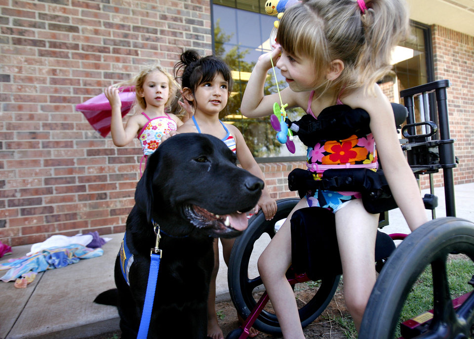 Photo - Landry Lewis, right, Leah Perry, middle, and Olivia Tedesco play with Costa, a therapy dog, at Special Care Inc. in Oklahoma City Friday, July 24, 2009. By Ashley McKee, The Oklahoman ORG XMIT: KOD
