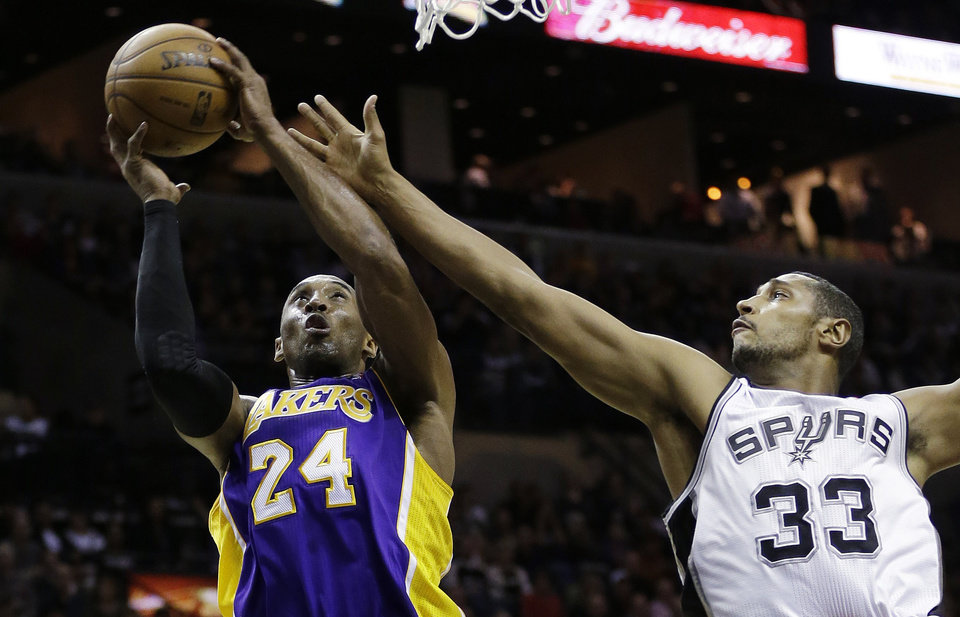 Los Angeles Lakers' Kobe Bryant (24) pulls down a rebound in front of San Antonio Spurs' Boris Diaw (33), of France, during the first quarter of an NBA basketball game on Wednesday, Jan. 9, 2013, in San Antonio. (AP Photo/Eric Gay)