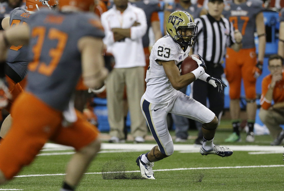 Photo - Pittsburgh punt returner Tyler Boyd (23) runs back a kick 54 yards for a touchdown during the first half of the Little Caesars Pizza Bowl NCAA college football game against Bowling Green, Thursday, Dec. 26, 2013, in Detroit. (AP Photo/Carlos Osorio)