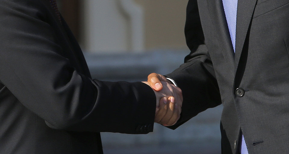 Photo - U.S. President Barack Obama, right, shakes hands with Russia's President Vladimir Putin during arrivals for the G-20 summit at the Konstantin Palace in St. Petersburg, Russia on Thursday, Sept. 5, 2013. The threat of missiles over the Mediterranean is weighing on world leaders meeting on the shores of the Baltic this week, and eclipsing economic battles that usually dominate when the G-20 world economies meet. (AP Photo/Dmitry Lovetsky)