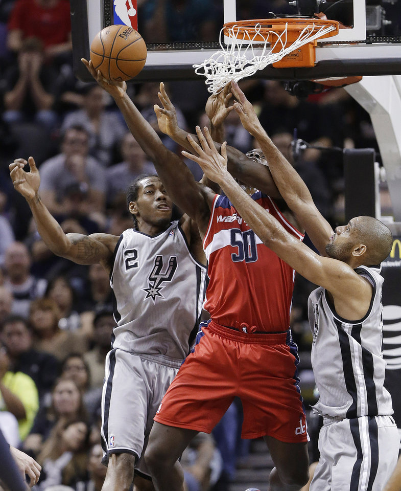 Photo - Washington Wizards' Emeka Okafor (50) works between San Antonio Spurs' Kawhi Leonard (2) and Tim Duncan, right, during the first half of an NBA basketball game, Saturday, Feb. 2, 2013, in San Antonio. (AP Photo/Eric Gay)