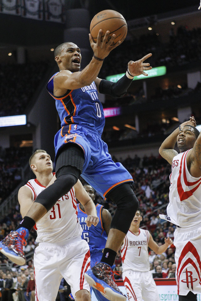 Oklahoma City Thunder guard Russell Westbrook (0) drives to the basket for a layup past Houston Rockets center Cole Aldrich (31) and forward Marcus Morris, right, during the first half of an NBA basketball game, Saturday, Dec. 29, 2012, in Houston. (AP Photo/Bob Levey)