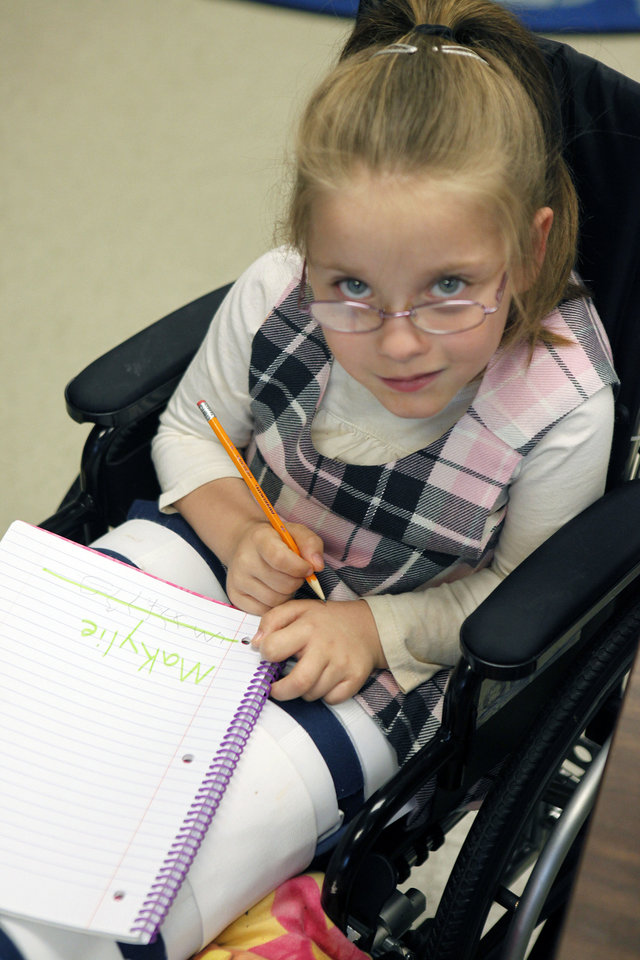 Photo - Special needs student McKiley Newlin works on penmanship in instructor Angie Absher's class at Johnson Elementary School. Photo by Paul Hellstern, The Oklahoman  PAUL HELLSTERN
