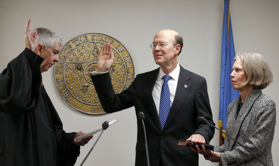 Chief Justice Steven W. Taylor swears in Bob Anthony to his fifth term on the Oklahoma Corporation Commission on Thursday. Anthony�s wife, Nancy, holds the Bible.