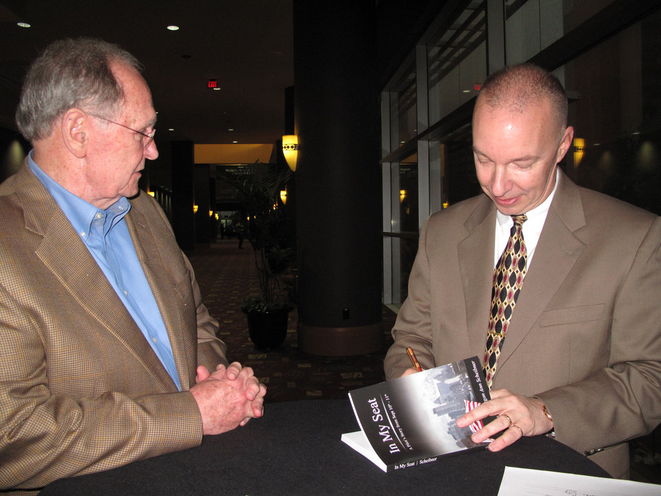 Photo - David Thomas of Oklahoma City watches as Steve Scheibner signs a copy of the book