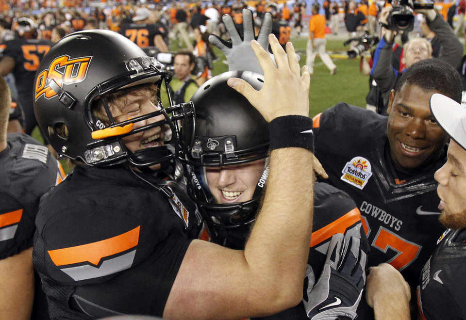Photo - Oklahoma State's Quinn Sharp, middle, celebrates his game-winning field goal with teammates, including Connor Sinko, left, after the Fiesta Bowl NCAA college football game against Stanford Monday, Jan. 2, 2012, in Glendale, Ariz.  Oklahoma State defeated Stanford 41-38 in overtime.(AP Photo/Ross D. Franklin) ORG XMIT: PNP146