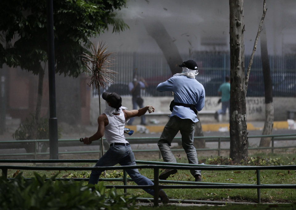 Photo -   Relatives of inmates protesting against measures taken by authorities to control a riot at the La Planta prison clash with National Guard soldiers outside the jail in Caracas, Venezuela, Thursday, May 17, 2012. Gunfire erupted on Thursday inside the prison where armed inmates have prevented security forces from retaking control for nearly three weeks. (AP Photo/Ariana Cubillos)