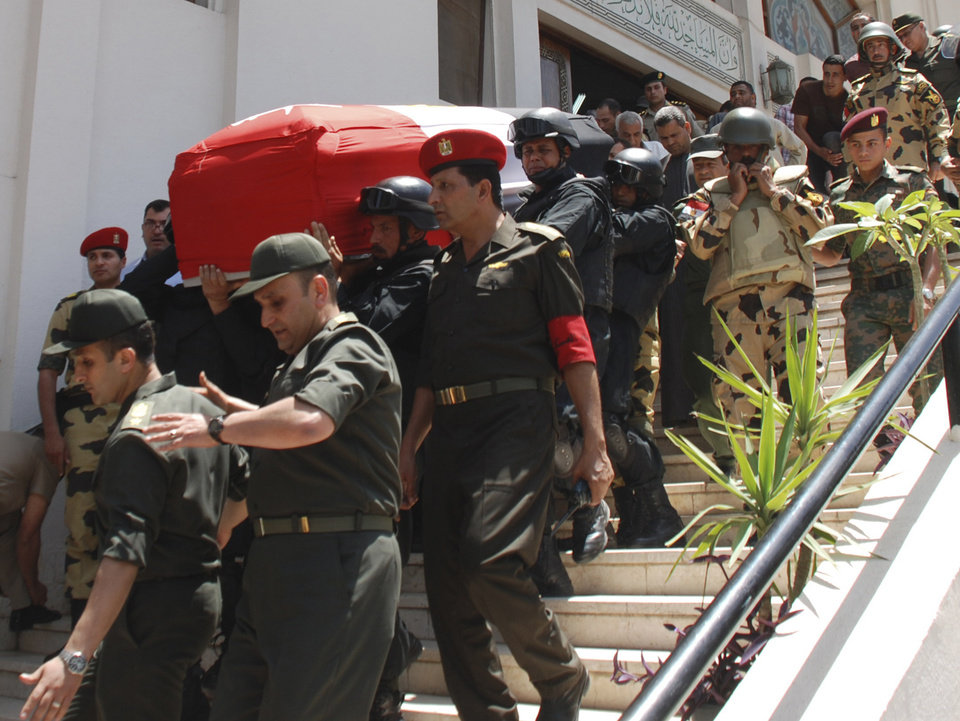 Photo -   Egyptian commandos carry the coffin of their comrade, Cpl. Samir Anwar Ismail, who was killed in clashes with protesters in Cairo, Egypt, Saturday, May 5, 2012. Lawyers say authorities have detained over 300 Egyptian protesters including 18 women following clashes outside the country's Defense Ministry, accused of attacking troops and disrupting public order.(AP Photo)