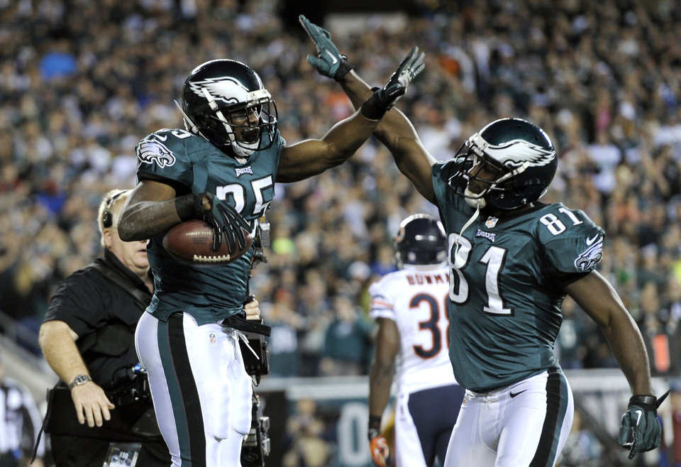 Photo - Philadelphia Eagles' LeSean McCoy, left, celebrates with Jason Avant after McCoy's touchdown during the first half of an NFL football game against Chicago Bears, Sunday, Dec. 22, 2013, in Philadelphia. (AP Photo/Michael Perez)