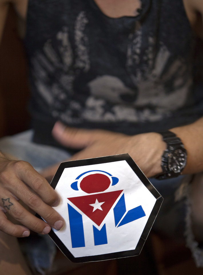 Photo - In this July 11, 2014, photo, Manuel Barbosa, 25, shows the logo of his