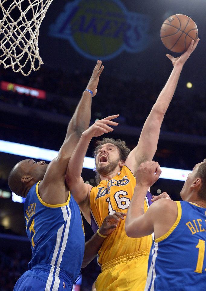Los Angeles Lakers forward Pau Gasol, center, of Spain puts up a shot as Golden State Warriors forward Carl Landry, left, defends during the first half of their NBA basketball game, Friday, Nov. 9, 2012, in Los Angeles. (AP Photo/Mark J. Terrill)