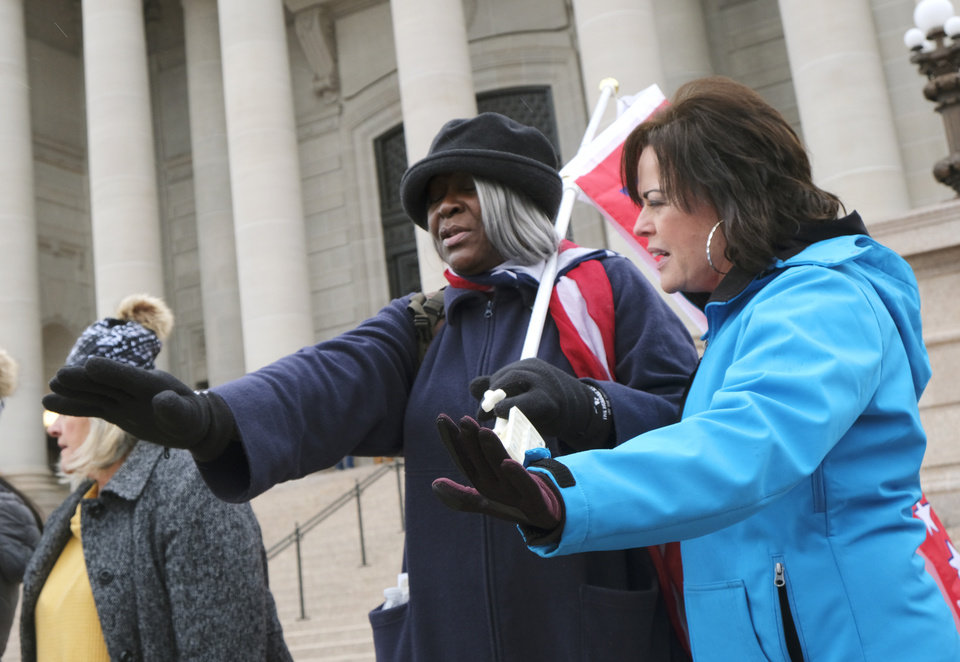 Photo - Two women pray for a man that had a medical emergency during the rally. Supporters of Pres. Donald Trump gathered at the Drive for 45 rally on the south plaza at the Capitol Wednesday, January 6, 2021. [Doug Hoke/The Oklahoman]
