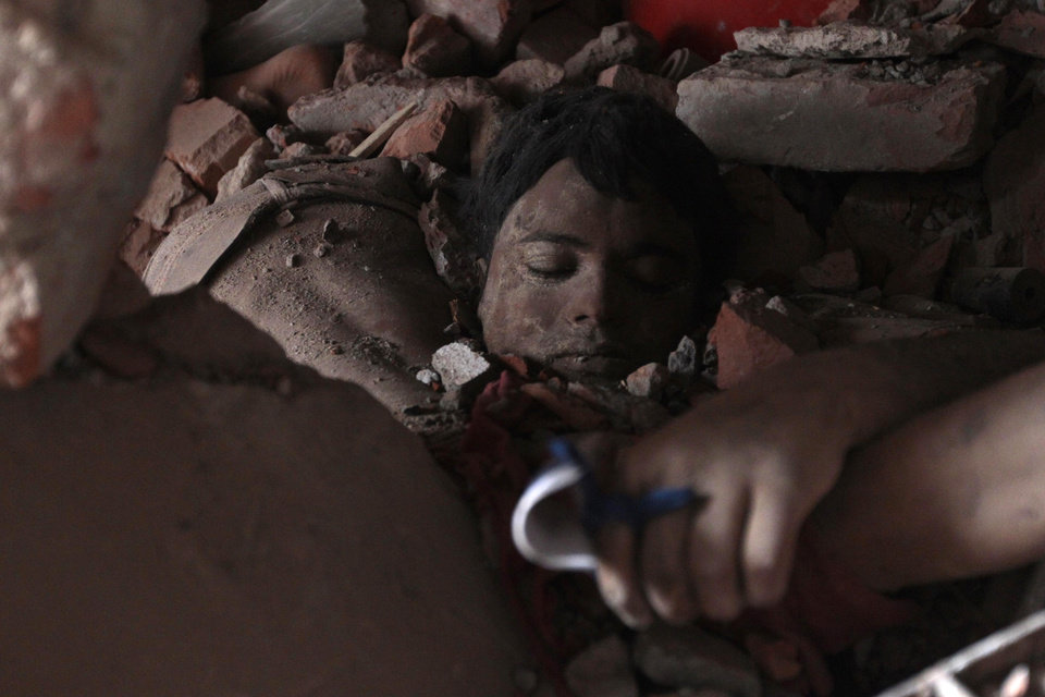 Photo - AP10ThingsToSee - A victim's body lies amid rubble at the site of a collapsed garment factory in Savar, Bangladesh,Thursday, April 25, 2013.  By Thursday, the death toll reached at least 194 people as rescuers continued to search for injured and missing, after a huge section of the eight-story building splintered into a pile of concrete. (AP Photo/A.M.Ahad)