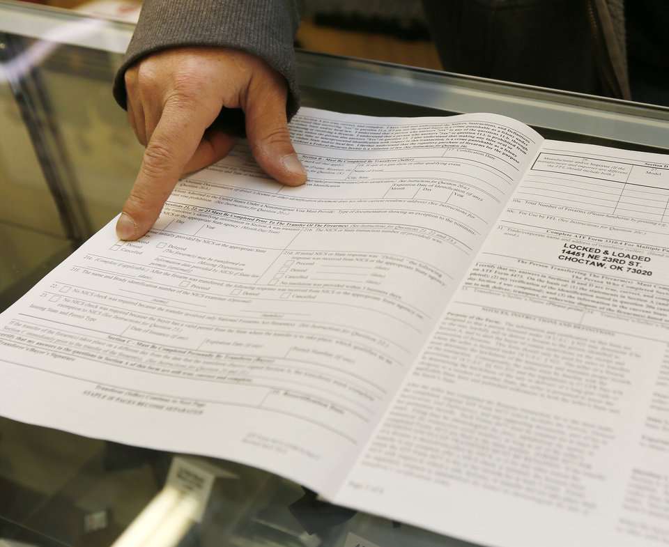 Darren Burger, co-owner of Locked and Loaded, shows the paperwork for a background check, a Form 4473 Firearms Transaction Record, at the store in Choctaw. Photo by Nate Billings, The Oklahoman