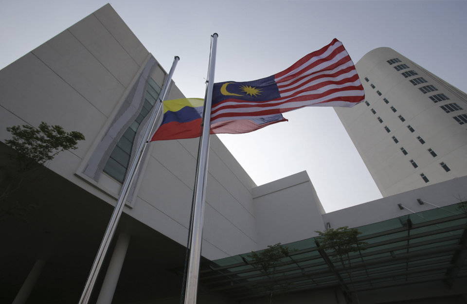 Photo - The Malaysian flag, right, and Putrajaya flag are placed on half-mast outside a hotel where relatives of passengers on board the missing Malaysia Airlines Flight MH370 are staying in Putrajaya, Malaysia on Thursday, March 27, 2014. Planes and ships searching for the downed Malaysia Airlines jetliner failed Thursday to find any of the 122 objects spotted by satellite before being forced by heavy rain, winds and low clouds to return to base after only a few hours. The flags are on half-mast to show solidarity and empathy with the family members of the passengers and crew of flight MH370. (AP Photo/Aaron Favila)