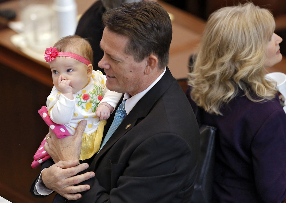 Photo - Rep. George Faught, of Muskogee, carries his granddaughter, Carmen Elise, as he shows her off to fellow lawmakers before the start of a joint session of the legislature where Gov. Mary Fallin delivered her 2016 State-of-the-State address at the Oklahoma state capitol on Monday, Feb. 1, 2016, in Oklahoma City, Okla. Photo by Jim Beckel, The Oklahoman