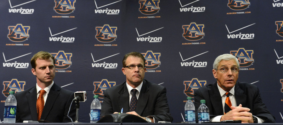 Auburn NCAA college footall coach Gus Malzahn, center,  listens while his newly named defensive Ellis Johnson, right, and offensive coordinator Rhett Lashlee, left, speak during a news conference on Friday, Dec. 7, 2012 in Auburn, Ala.(AP Photo/Todd J. Van Emst)