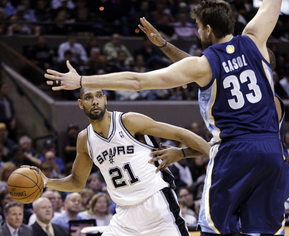 San Antonio Spurs' Tim Duncan (21) looks to pass around Memphis Grizzlies' Marc Gasol (33) during the second quarter of an NBA basketball game, Wednesday, Jan. 16, 2013, in San Antonio. (AP Photo/Eric Gay)