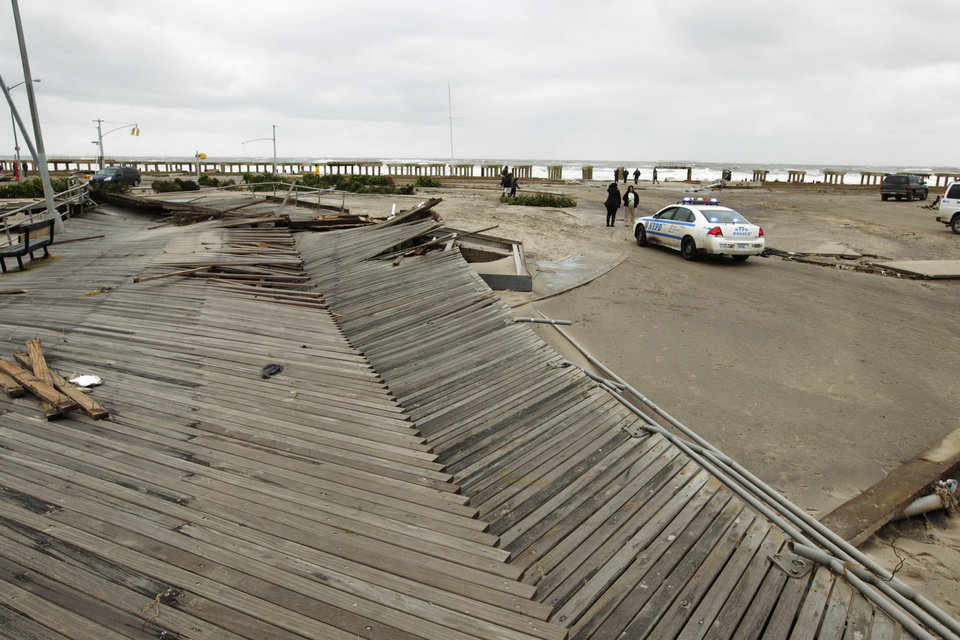Pedestrians asses the damage from flooding near Rockaway Beach in the New York City borough of Queens Tuesday, Oct. 30, 2012, in New York. Sandy, the storm that made landfall Monday, caused multiple fatalities, halted mass transit and cut power to more than 6 million homes and businesses. (AP Photo/Frank Franklin II) ORG XMIT: NYFF147