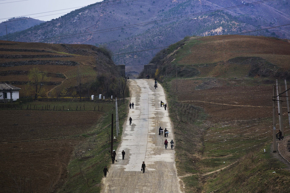 Photo - In this April 23, 2013 photo, North Koreans walk along a rural road north of Kaesong, North Korea. (AP Photo/David Guttenfelder)
