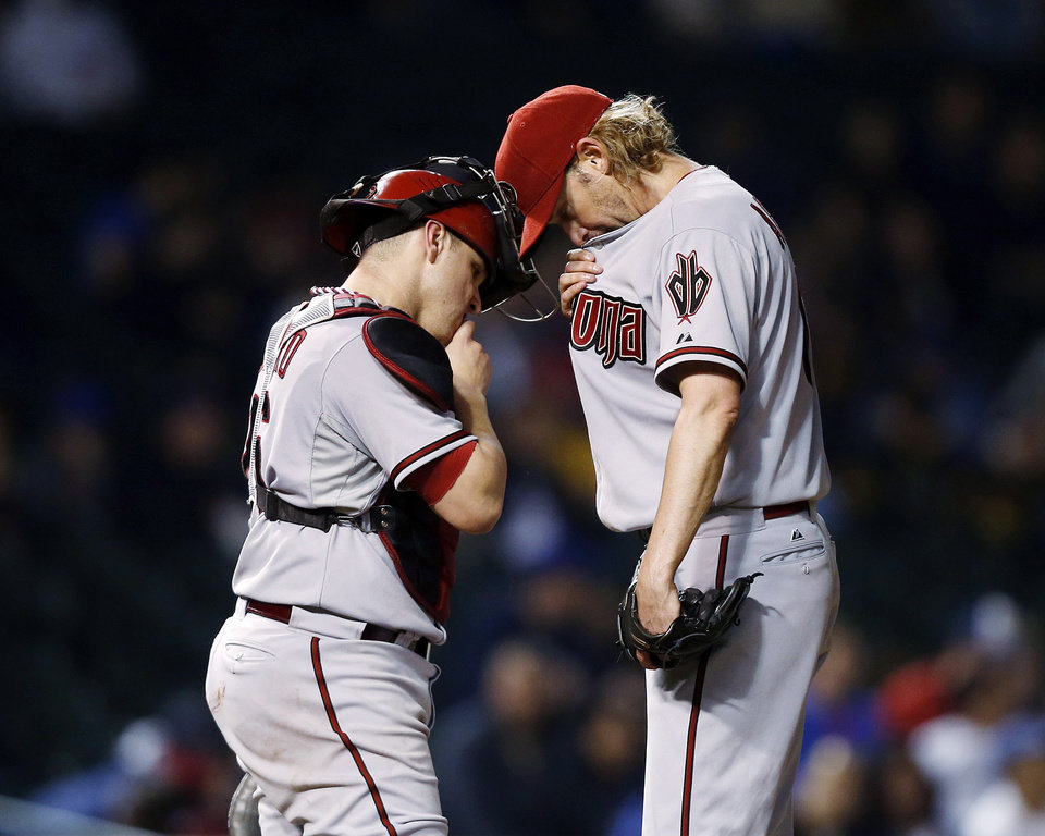 Photo - Arizona Diamondbacks starting pitcher Bronson Arroyo, right, and catcher Miguel Montero meet on the mound during the sixth inning of a baseball game against the Chicago Cubs on Monday, April 21, 2014, in Chicago. (AP Photo/Andrew A. Nelles)